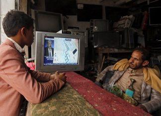 Πατέρας και γιος παρακολουθούν την είδηση της επίθεσης στην τηλεόραση